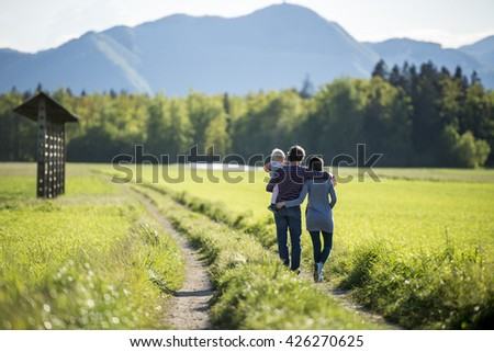 View from behind of a young family - husband holding a toddler and hugging his wife - standing on a country road surrounded by green meadow with forest and mountains in background. - stock photo