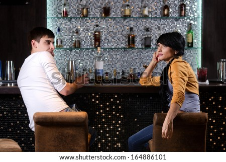 View from behind of a young man and woman chatting at the bar turning to face each other on their barstools as they spend a relaxing evening at a nightclub - stock photo