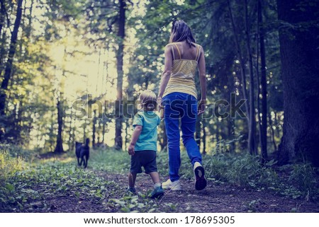View from behind of a young mother and child walking a dog along a footpath in the forest with a retro faded and toned effect. - stock photo