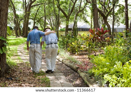 View from behind of an adult son walking with his senior father in the park. - stock photo