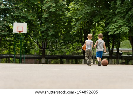 View from behind of two young boys walking across a basketball court together towards a distant goalpost backed by leafy green trees - stock photo