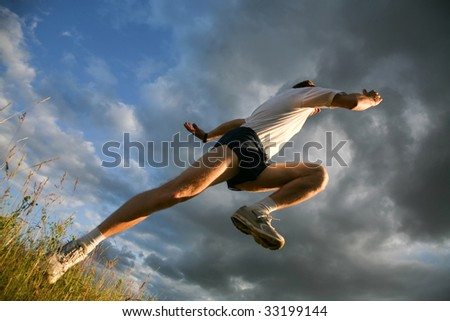 View from below: athlete raising leg and hand - stock photo