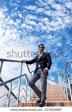 View from below of a businessman dressed in luxury clothes standing with a cigarette against blue sky background with copy space for your advertising, young men entrepreneur smoking during work break - stock photo