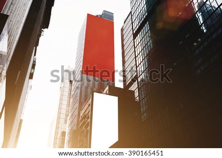 View from below of a tall skyscrapers with advertising billboards with copy space for your advertising text message or promotional content. High-rise modern buildings in business center of big city - stock photo