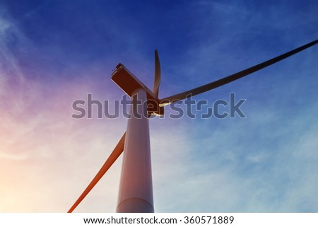 View from below of a wind turbine against beautiful cloudy sky and sun rays, electric generator with heaven on background, windmill outside the city, renewable energy sources  - stock photo