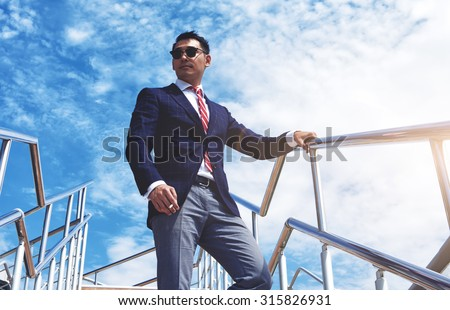 View from below of a young successful managing director standing with a cigarette outdoors against blue cloudy sky, confident businessman dressed in luxury suit relaxing after meeting or conference