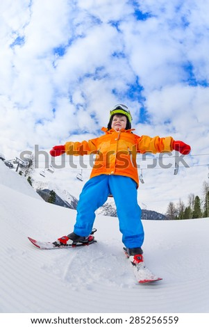 View from below of boy wearing ski mask and helmet skiing on Sochi ski resort Krasnaya polyana in Russia - stock photo