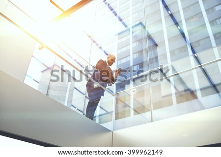 View from below of businessman is reading financial news on web page via cell telephone, while is standing in modern skyscraper interior. Confident male CEO is using mobile phone during work break - stock photo
