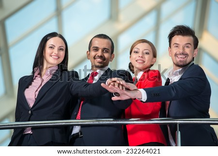 View from below of several business people are showing unity with their hands together. - stock photo