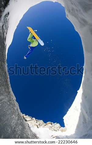 View from below of snowboarder jumping over rocky mountainside in winter - stock photo