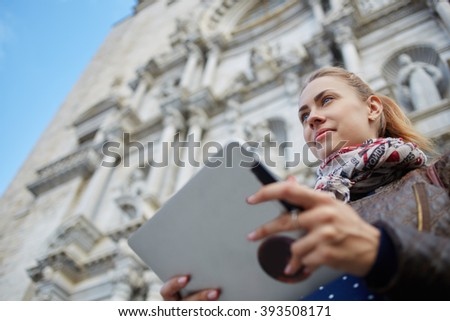 View from below of young charming woman is holding portable touch pad with copy space for your advertising text message. Female tourist is using digital tablet for navigation during walking outdoors - stock photo