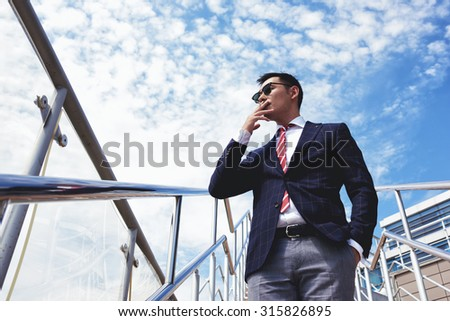 View from below of young confident businessmen smoking cigarette while standing outside office, successful managing director dressed in stylish clothes relaxing outdoors after hard work day - stock photo