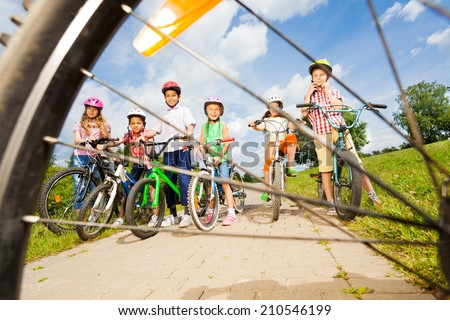View from bicycle spoke on kids with helmets - stock photo