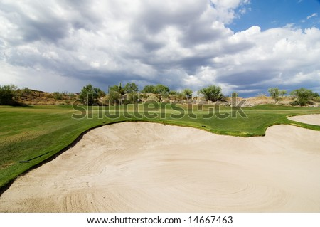 View from bunker sand trap of golf course hole with stunning desert landscape and dramatic cloud scape. - stock photo