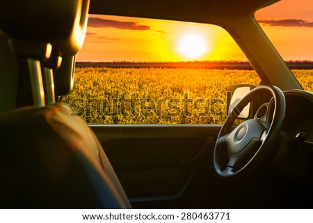 view from car window on field at sunset - stock photo
