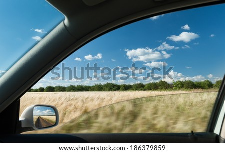 view from car window on wheat field - stock photo
