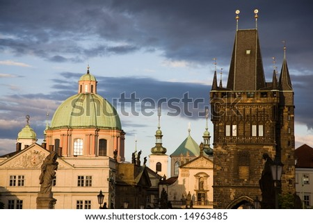 View from Charles bridge with sculptures to the New Town church towers with cloudscape on the background.