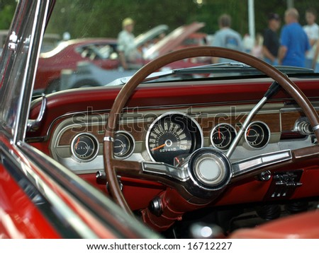 View from classic red convertible through windshield at a car show - stock photo