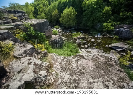 View from cliff on fast mountain river and forest - stock photo
