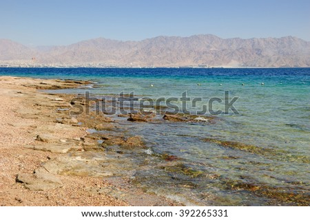 View from Eilat's Coral Beach towards Aqaba in Jordan (Eilat. Israe). Coral Beach Nature Reserve in Eilat, one of the most beautiful coral reef in the world, is famous tourist and diver attraction. - stock photo