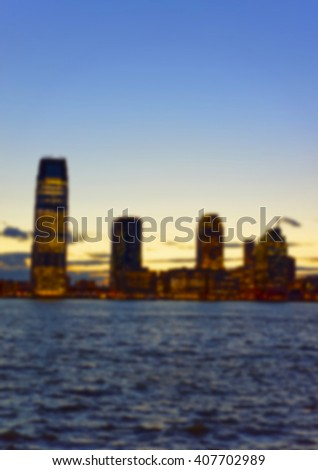 View from Esplanade of Lower Manhattan, New York, USA, on skyline in Paulus Hook, Jersey City, New Jersey, USA. Skyscrapers illuminated in the evening. On Hudson River. Blurred. - stock photo