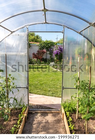 View from greenhouse on beautiful formal garden - stock photo