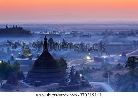 View from hazy sunset over silhouette Ratanabon Paya in Mrauk-U, Myanmar. - stock photo