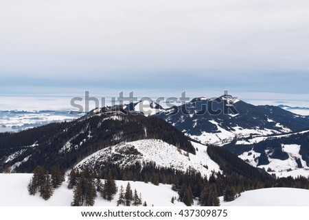 View from highest point of ski hill on rugged alpine forests and mountains under gray storm clouds - stock photo