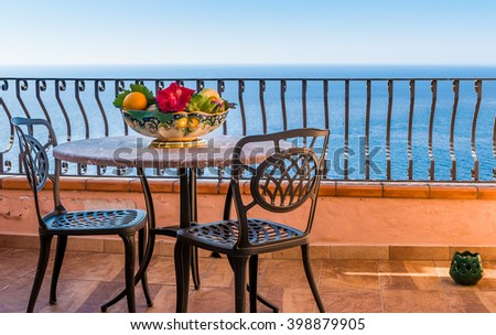 View from hotel room luxury and elegant mediterranean terrace with fruit and floewr bawl in morning sun, Sicily, Italy - stock photo