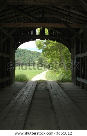 View From Inside a Covered Bridge Showing a Winding Country Road - stock photo