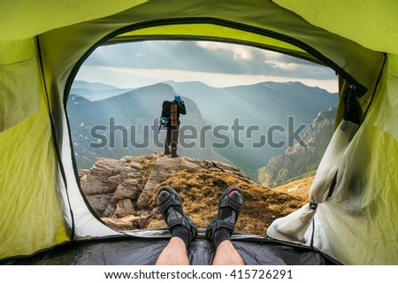View from inside a tent on the young man on a rock and beautiful mountains in Macedonia - stock photo