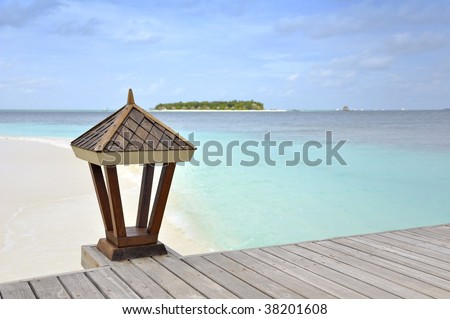 View from jetty over turquoise ocean with a wooden lantern in foreground. - stock photo
