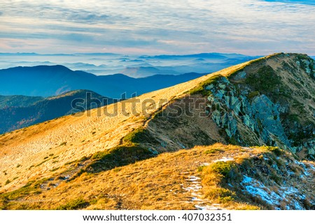 View from mountain ridge with yellow grass to sunset hills - stock photo