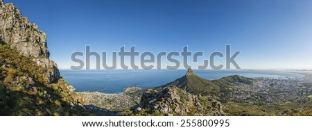 View from one of the many hiking routes up Cape Town's Table Mountain. Lions Head and Cape Town city in distance as sun rises over the city. Very popular daily activity for both locals and tourists. - stock photo