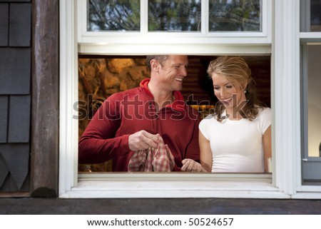 View from outside a window of a smiling couple doing dishes together in their kitchen. Horizontal format. - stock photo