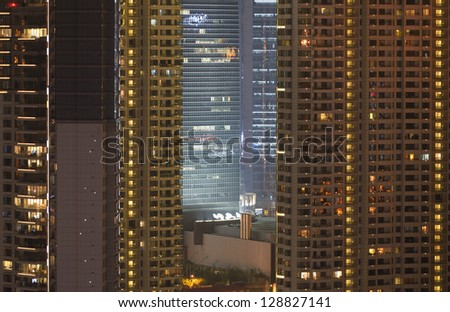 View from Puxi side on Pudong financial center. Illuminated office and hotel skyscrapers by night. High iso, grain. - stock photo
