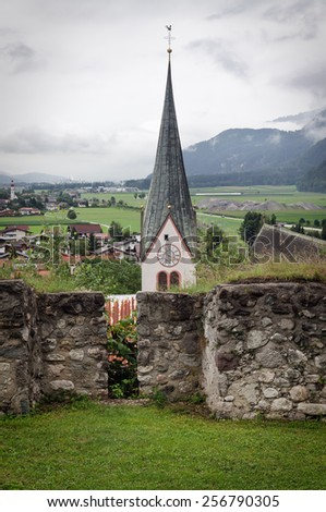 View from ruins of Rattenberg castle to the spire of the parish church of Rattenberg and landscape, Tyrol, Austria. Photo with vignette. - stock photo