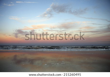 View from sandy beach of picturesque red sunset, horizon over sea - stock photo