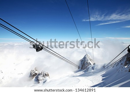 View from ski lift above clouds in the Dolomites of Italy