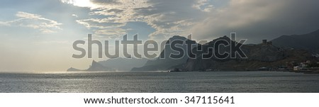 View from Sudak toward New World with plume of spray raised by stormy wind above water beyond Crab Island, with Genoese Fortress, Sokol Mountain, Eagle Mountain and Kapchik Cape, Crimea, Russia. - stock photo
