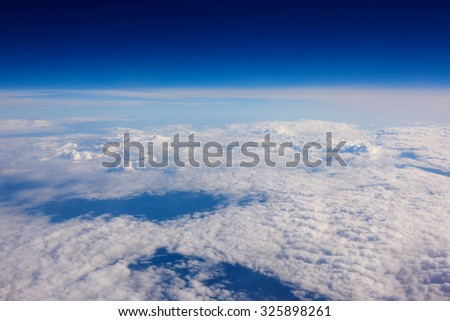 View from the airplane of a fluffy calm clouds and bewitching sky background with copy space for your text message or promotional content, advertising field - stock photo