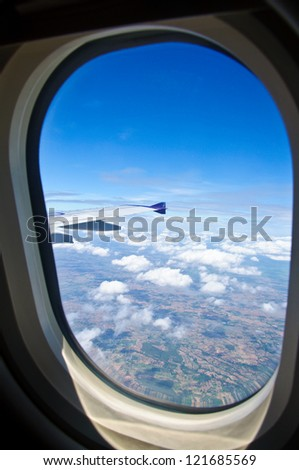 View from the airplane seat - window with sky, clouds - stock photo