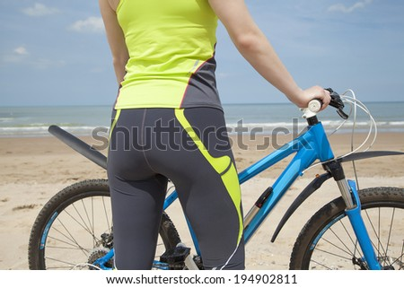 View from the back at the girl in a green jumpsuit with a blue bicycle on the beach - stock photo
