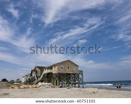 View from the beach showing a beautiful cloudscape and the sand bags around a row of condemned homes in Nags Head North Carolina in the Outer Banks. - stock photo