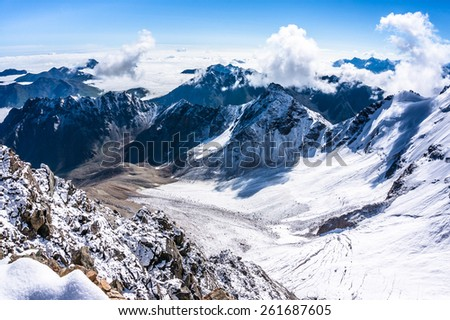 View from the bird's-eye over the mountains and clouds from Uku pass.Glacier below. Picture was taken during trekking hike in the beautiful Caucasus mountains, Bezengi region,Kabardino-Balkaria,Russia - stock photo