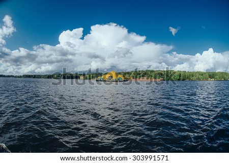 View from the board of a sailing yacht on the waters, sailing ships and the forest growing along the coast, as well as people's homes. View from the boat nose of the surrounding water spaces and the  - stock photo