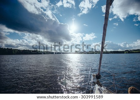 View from the board of a sailing yacht on the waters, sailing ships and the forest growing along the coast, as well as people's homes. View from the boat nose of the surrounding water spaces  - stock photo