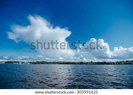 View from the board of a sailing yacht on the waters, sailing ships and the forest growing along the coast, as well as people's homes. Expanse of water reservoirs, beautiful cloud drifting over - stock photo