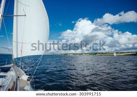 View from the board of a sailing yacht on the waters, sailing ships and the forest growing along the coast, as well as people's homes. The yacht is going full speed under sail.