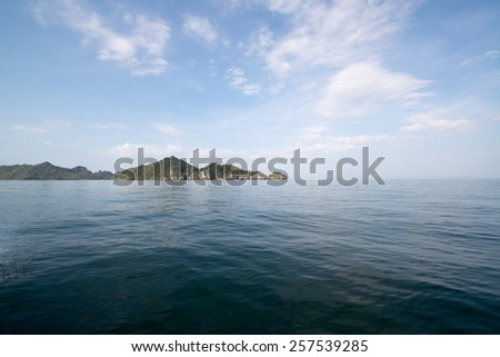 View from the boat. Sea with the bright blue sky and mountains in background